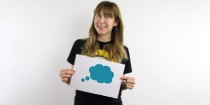 Young woman holding a piece of paper with a thought bubble drawn on it